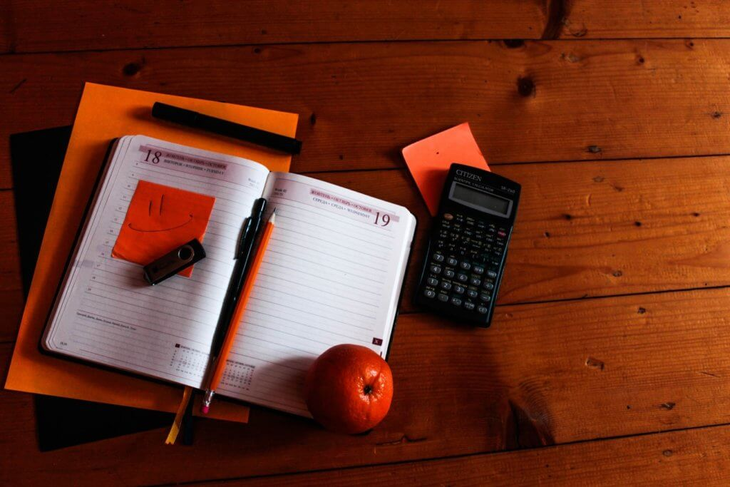 A notebook, calculator, and other supplies on a desk