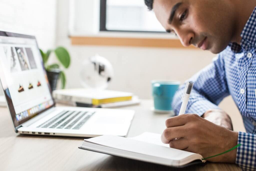 man working in notebook with laptop open