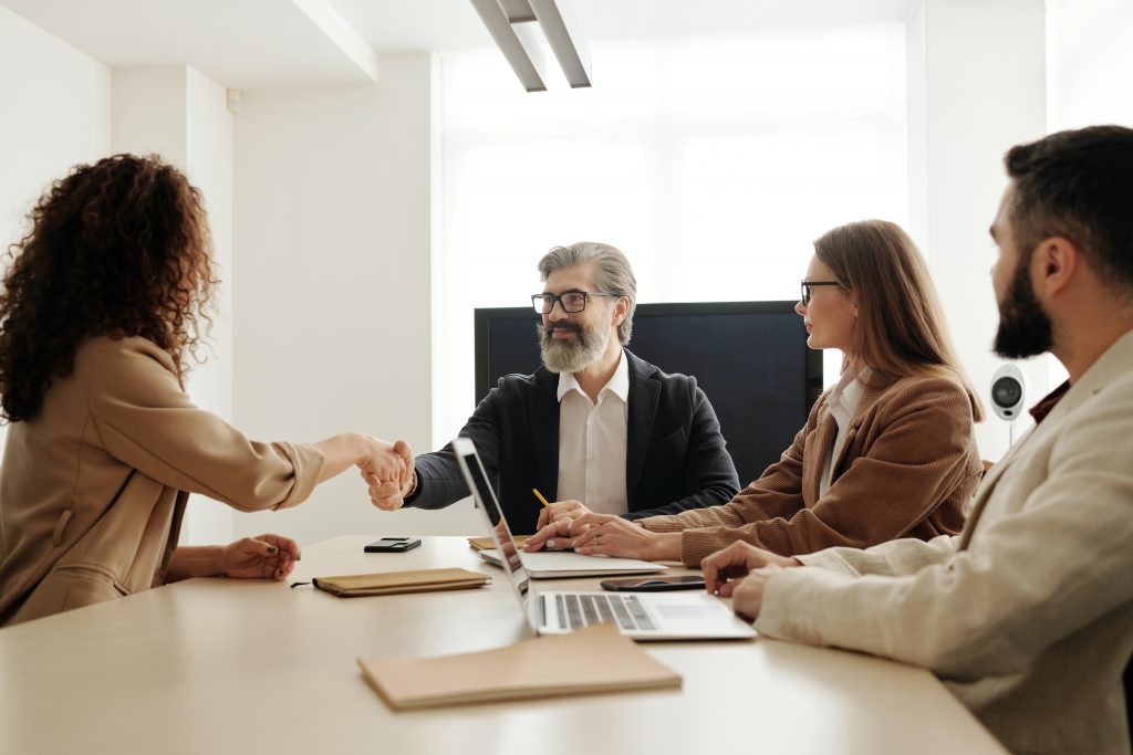 Woman interviewing in front of three people for a new healthcare job