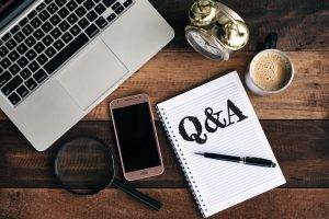 questions and answers written on a notepad on a wooden desk with a laptop